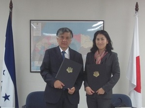 H.E. Mr. Kenji OKADA (Ambassador of Japan to Honduras) and Ms. Rumiko YAMADA (Country Director of AMDA-MINDS Honduras) exchange the project contract under the Grant Assistance for Japanese NGO Scheme.