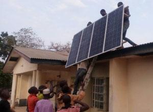 皆で協力してソーラーパネルを屋根に上げる