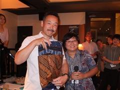 当選者にインドネシアのお土産をプレゼントする梶田事業統括(右)