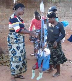 GMPスポットで、体重測定を行っている保健ボランティア(左)。子どもの成長の様子を記録し、低栄養の子どもの早期発見などにつなげます。