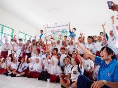 スクールミルクプログラムを実施している小学校の子どもたちと一緒に牛乳を飲む筆者(右端)