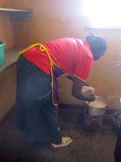 ザンビア人の主食、シマをつくっているお母さん。料理時の姿勢も腰を大きく曲げています。