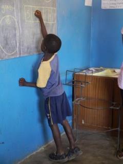 Grade1のクラス。算数の順番に関する問題に回答する男子生徒。つま先立ちになって、黒板に向かっています。