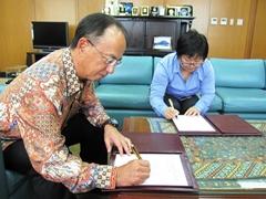 贈与契約書に署名する鹿取大使(左)と梶田未央統括(右)