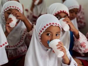 地元で搾乳・加工された牛乳を飲む小学校の子ども達。子どもたちは週に3日の牛乳配布の日が楽しみ。この日は農作業を手伝わせず学校に行かせる親御さんも多いとか。