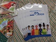 9日の報告会で、クリアファイルと一緒に、大使からいただいたポストカードなどを参加者にプレゼントしました