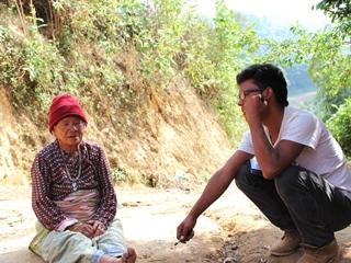 ②ワルティンVDCのおばあさんと話をするマノーズ君(右)