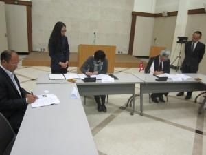 署名する町田臨時代理大使と松本