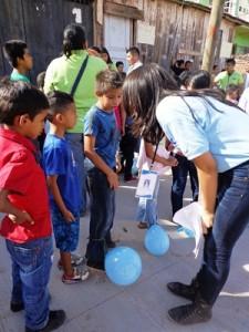 子どもたちに風船割りゲームの説明をするコミュニティリーダー