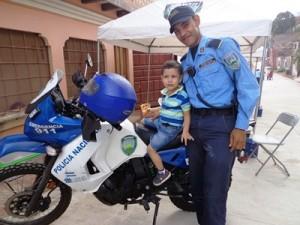 地域警察官のバイクに乗せてもらう地域の子ども