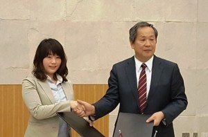 契約を交わす統括の小林(左)と小川大使(右)