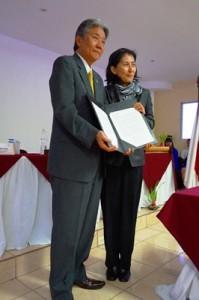 署名された契約書を手にする松井大使(左)と山田統括