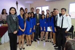 君が代等を合唱したコーラス部員と記念撮影する松井大使、山田統括