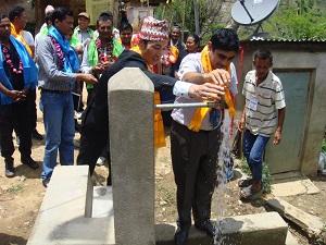 完成式典で蛇口を開栓する國貞書記官(左)とコマル・ダマル郡開発局長