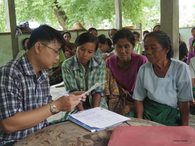 融資申請をする村人と確認するスタッフ