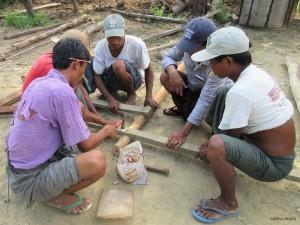 トイレ小屋のフレームとなる木材を組み立てる村人